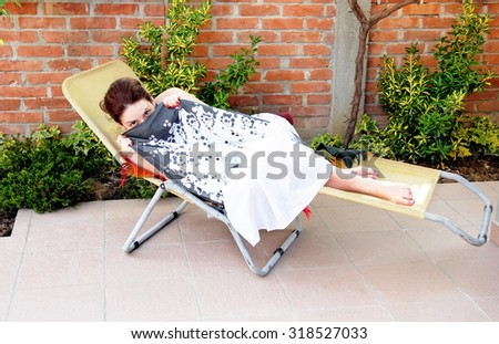 young caucasian woman lying in outdoor chair hiding by her skirt - stock photo