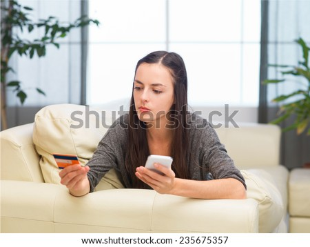 young caucasian woman making online purchase over the phone from home - stock photo