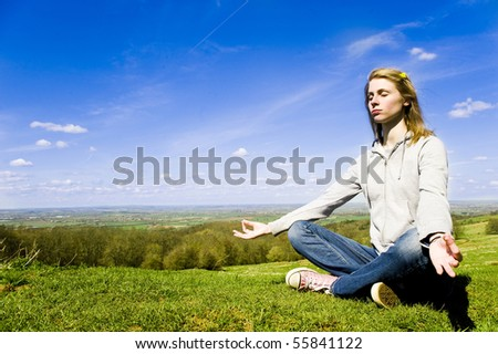 Young caucasian woman meditating outdoors in front of a bright blue sky and green countryside - stock photo