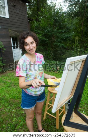 young caucasian woman painting on canvas outside - stock photo