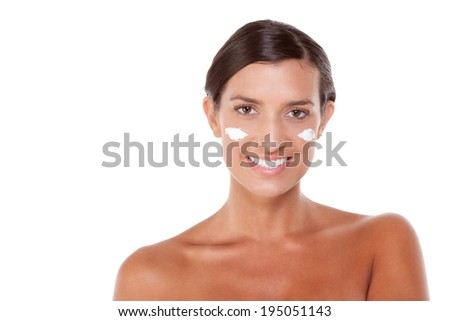 Young Caucasian woman putting cream on her face - stock photo