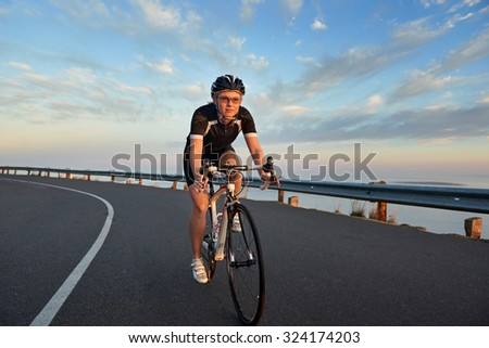 Young caucasian woman riding a bike on the road - stock photo