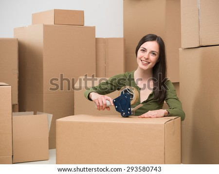 young caucasian woman sealing a cardboard box with adhesive tape. moving home - stock photo