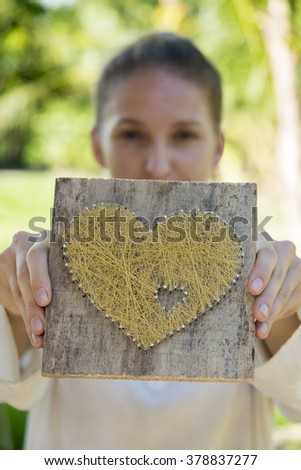 Young caucasian woman  showes symbolic heart - stock photo