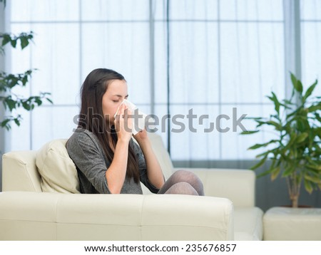 young caucasian woman sitting on couch at home, blowing nose with tissue - stock photo