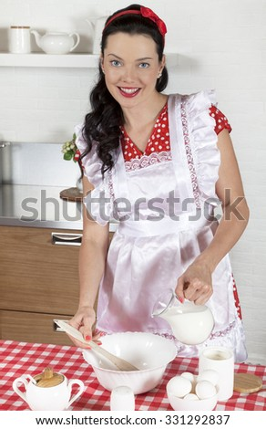 Young Caucasian woman standing by the table in the kitchen, cooking the meal - stock photo