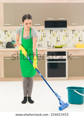 young caucasian woman standing in kitchen at home, washing floors with mop - stock photo