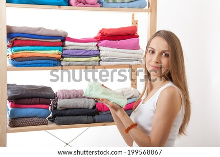 Young caucasian woman standing near the wardrobe and holding clothes - stock photo
