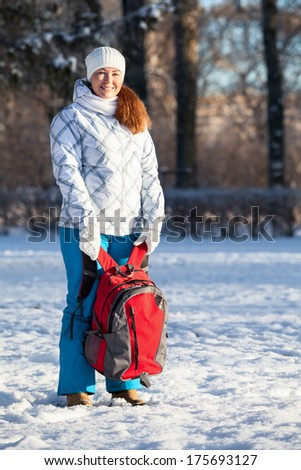 Young Caucasian woman standing with backpack in winter park - stock photo