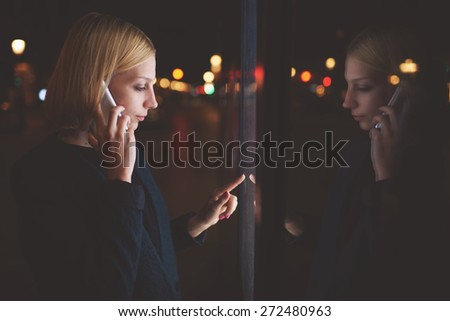 Young caucasian woman talking on cellphone while touching sensitive screen of smart city bus stop into the night, female using mobile banking or internet money payment through automated teller machine - stock photo