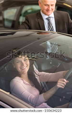Young Caucasian woman testing car in showroom - stock photo