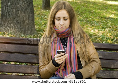 Young Caucasian woman with a cell phone, sitting in a park on a wooden bench, reading a SMS. Autumn around a lot of colorful foliage - stock photo