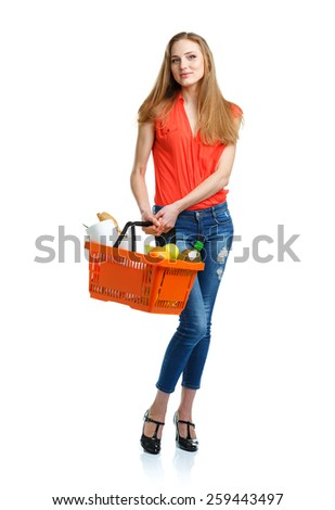 Young caucasian woman with assorted grocery products in shopping basket isolated on white background - stock photo