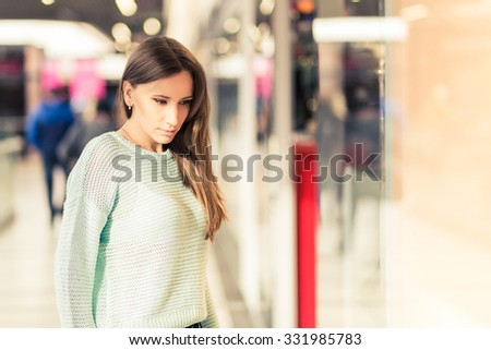 Young caucasian woman with dark brown hair looking through window in the mall. Window shopping background. Warm color toned image - stock photo