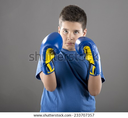 Young champion boy with blue boxing gloves. - stock photo