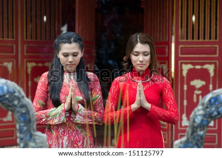 Young charming ladies praying in the Buddhist temple on the foreground - stock photo