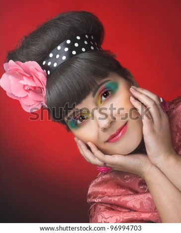 Young charming plump woman with artistic make-up and with pink flower in her hair. - stock photo