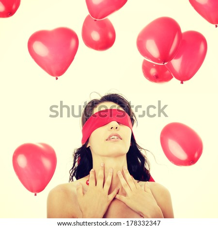 Young charming sensual woman blindfold with falling heart shaped baloons, over white - stock photo