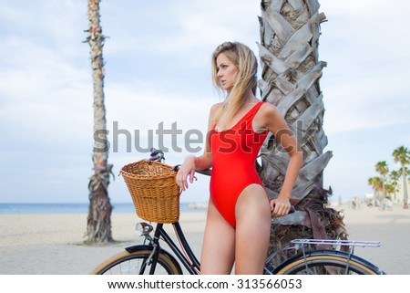 Young charming woman in bikini resting after ride on her retro bicycle along the beach, attractive female standing with vintage bike on coastline enjoying beautiful landscape of the sea in summer day - stock photo