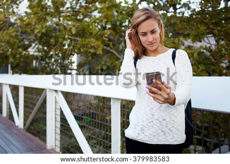 Young charming woman making photo via smart phone for social network while standing on a bridge in spring day, beautiful female student photographing herself on cell telephone against deciduous trees - stock photo