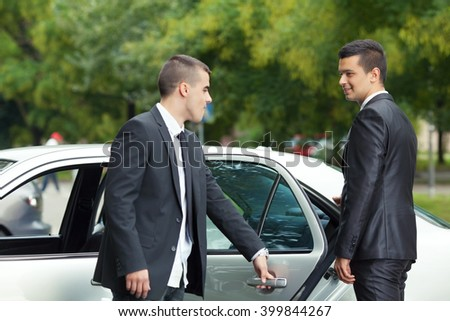 Young chauffeur is holding the door for the young businessman getting into the car - stock photo