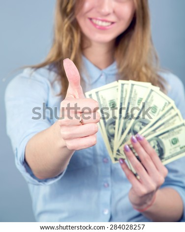 Young cheerful american businesswoman holding money and showing thumbs up in the blue background. Concept - thumb up, woman, dollar, dollar us. Happy young woman showing fun of dollars and thumbs up. - stock photo