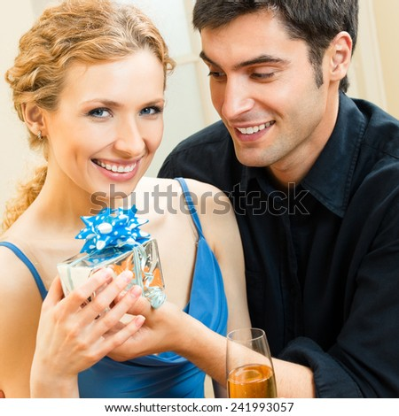Young cheerful attractive couple celebrating with champagne and gift, indoors - stock photo