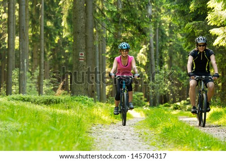 Young cheerful biker couple in woods - stock photo