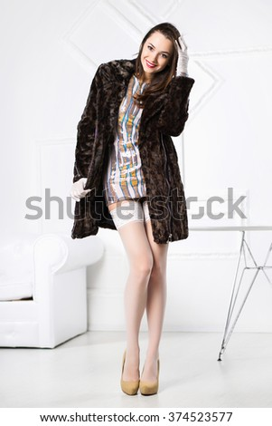 Young cheerful brunette posing in short dress and fur coat - stock photo