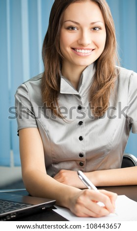 Young cheerful business woman writing at office - stock photo