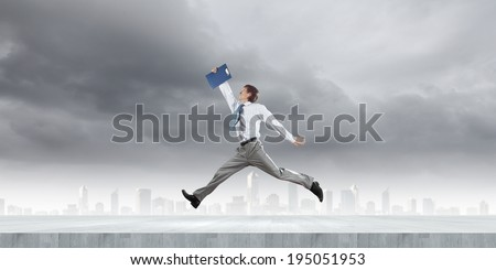 Young cheerful businessman in jump against city background - stock photo