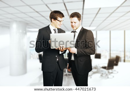 Young cheerful businessmen with laptop in hands standing on blurry conference room background with city view. Teamwork concept - stock photo