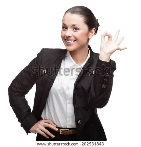 young cheerful caucasian brunette businesswoman in black suit showing ok isolated on white - stock photo