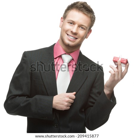 young cheerful caucasian businessman in black suit holding small red gift. isolated on white - stock photo