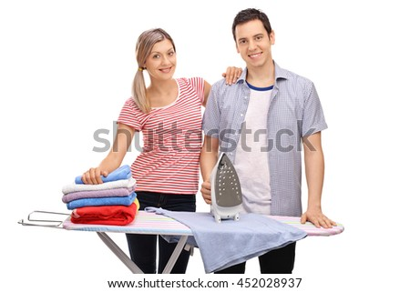 Young cheerful couple posing together behind an ironing board isolated on white background - stock photo