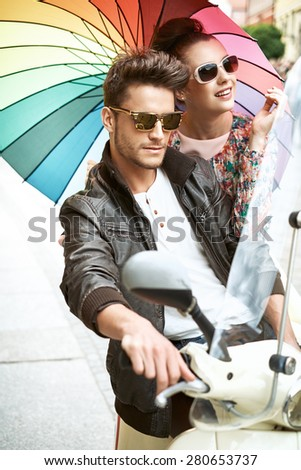 Young cheerful couple riding a scooter - stock photo