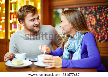 Young cheerful couple talking in cafe by cup of coffee - stock photo