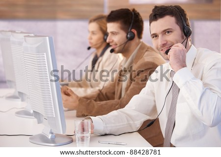 Young cheerful customer servicer working in call center, smiling.? - stock photo