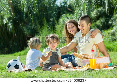 Young cheerful family with little daughters having holiday with picnic at park. Focus on man