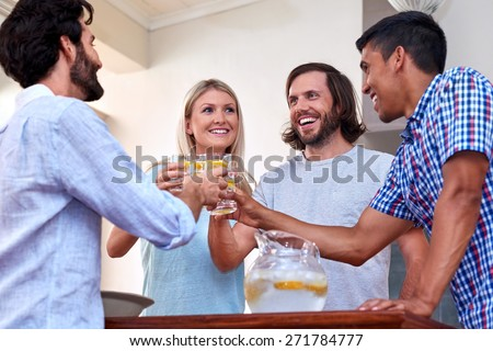 young cheerful friends toasting indoors at gathering - stock photo