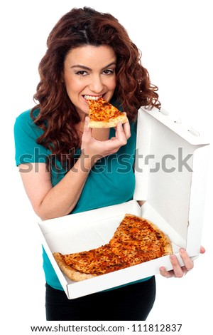 Young cheerful girl enjoying pizza alone. All on white background - stock photo