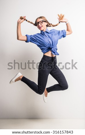 Young cheerful girl having fun and jumping. Smiling girl with hairstyle with pigtails. - stock photo