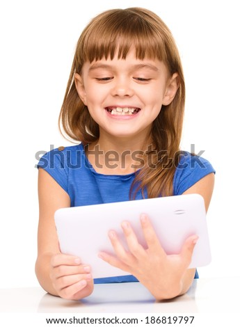 Young cheerful girl is using tablet while sitting at table, isolated over white - stock photo