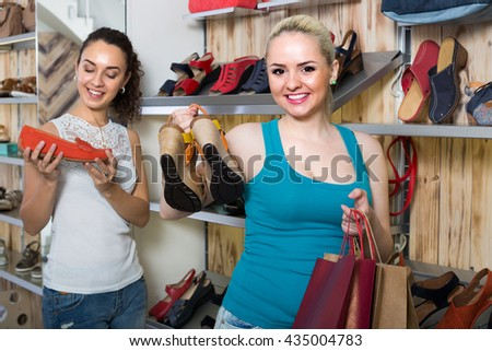 Young cheerful girl showing a chosen pair of shoes while her friend buying - stock photo