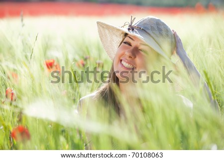 Young cheerful girl with hat staring at camera among green wheat. - stock photo