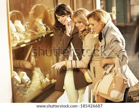 Young cheerful girlfriends looking at the jewellery - stock photo