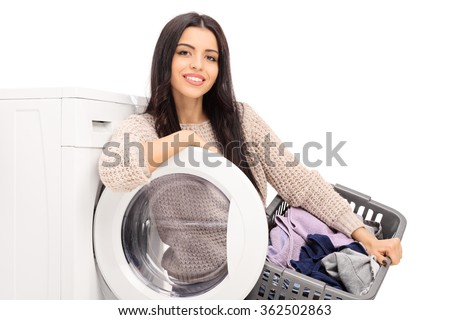 Young cheerful housewife holding a laundry basket and posing next to a washing machine isolated on white background - stock photo