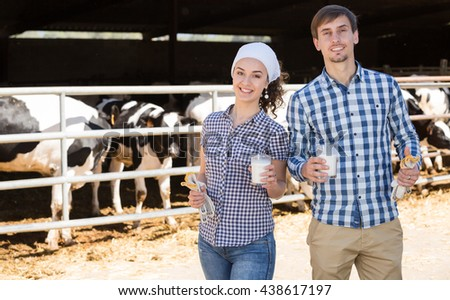 Young cheerful man and woman farmers standing with in the cow hangar and having fresh milk - stock photo