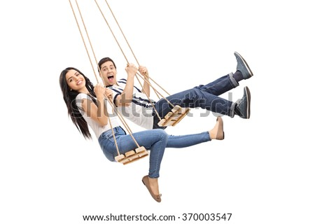 Young cheerful man and woman swinging on wooden swings isolated on white background - stock photo