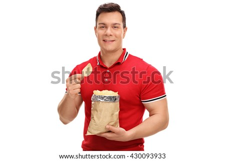 Young cheerful man eating potato chips and looking at the camera isolated on white background - stock photo
